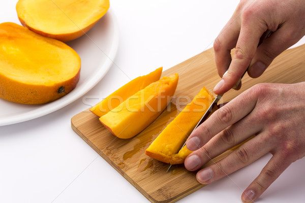 Mango Slice Being Cut Into Four Fruit Chips Stock photo © leowolfert