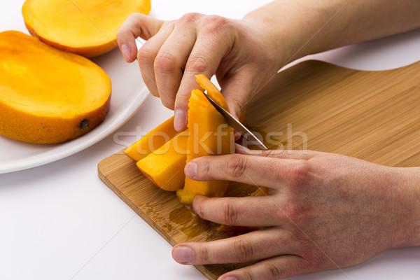 Peeling Off The Fruit Flesh From The Mango Skin Stock photo © leowolfert