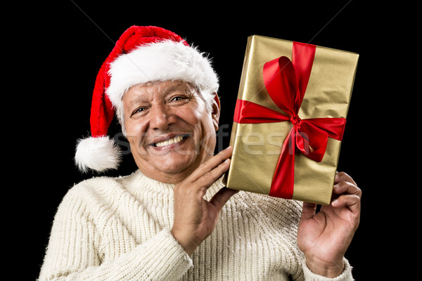 Smiling Old Man With Golden Gift Isolated On Black Stock photo © leowolfert