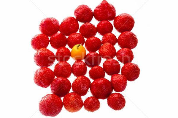 Single Kumquat In A Crowd Of Strawberry Fruits Stock photo © leowolfert