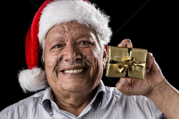 Old Gentleman With Red Hat Offering Golden Gift Stock photo © leowolfert
