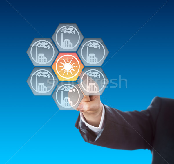 Business Hand Activating Solar Power Icon On Blue Stock photo © leowolfert
