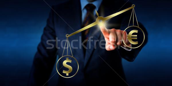 Dollar Outweighing The Euro On A Golden Balance Stock photo © leowolfert