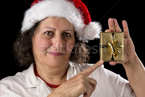 Mature Woman with Red Cap Pointing at Golden Gift Stock photo © leowolfert