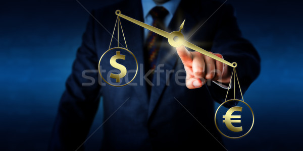 Euro Sign Outweighing The Dollar On Golden Scale Stock photo © leowolfert