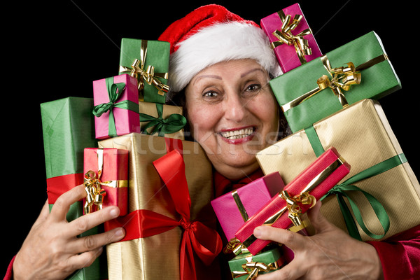 Delighted Old Lady Hugging a Dozen Wrapped Gifts Stock photo © leowolfert