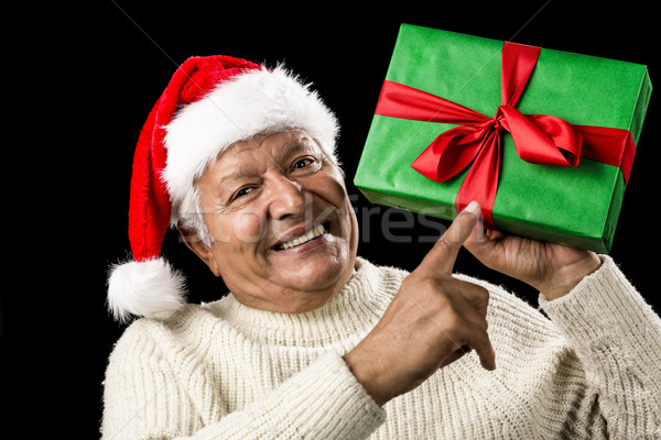 Old Man With Gentle Smile Pointing At Green Gift Stock photo © leowolfert