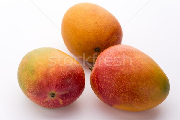 Three Ripe Mangos With Impeccable Skin On White Stock photo © leowolfert
