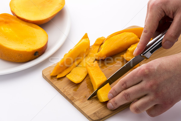 Two Hands Dicing A Mango Wedge With A First Cut Stock photo © leowolfert