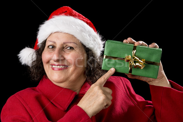 Smiling Mature Woman Pointing at Wrapped Xmas Gift