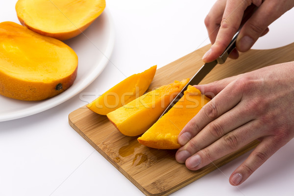 Mango Divided Into Thirds Being Subdivided Further Stock photo © leowolfert