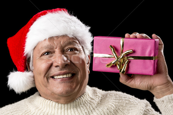 Excited Old Man With Santa Cap And Magenta Gift Stock photo © leowolfert