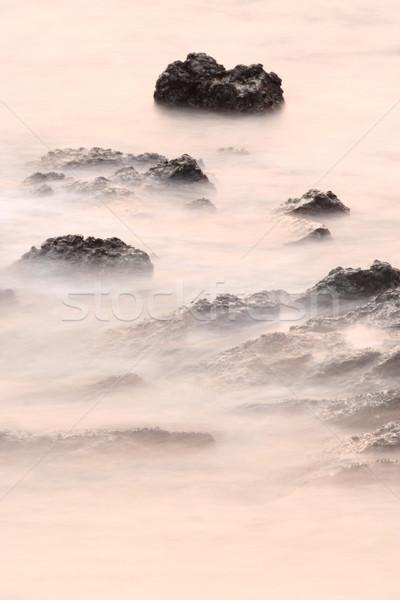 Longa exposição rocha costa pôr do sol paisagem fundo Foto stock © leungchopan