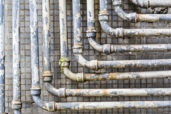 Series of parallel old pipes on wall Stock photo © leungchopan