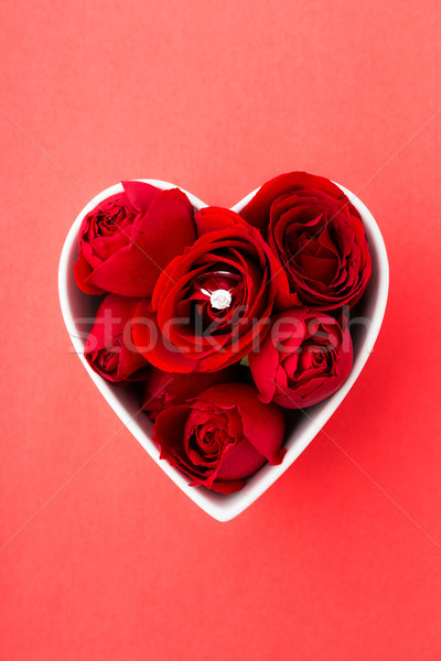 Red rose and diamond ring inside heart shape bowl over the red b Stock photo © leungchopan