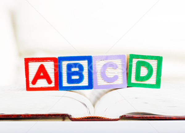 Alphabet block with ABCD on book Stock photo © leungchopan