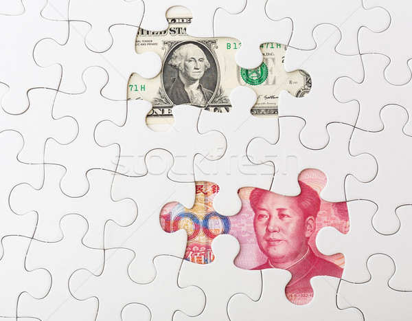 White puzzle with Chinese yuan and US dollar banknote Stock photo © leungchopan