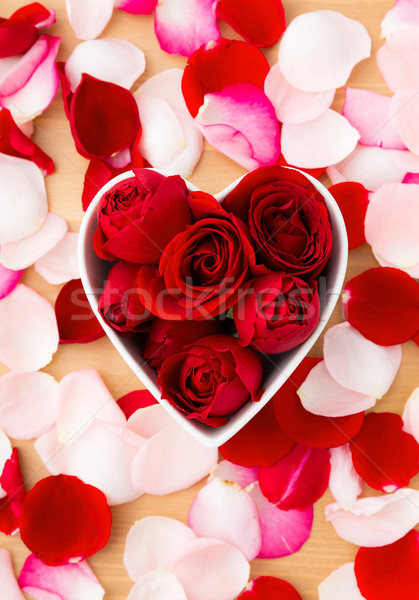 Red rose inside the heart shape bowl with pink petal beside Stock photo © leungchopan