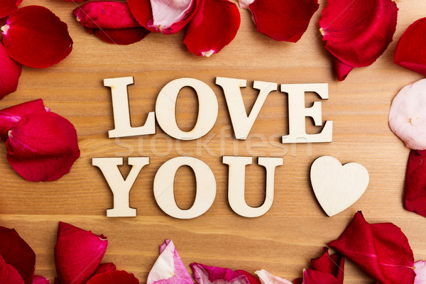 Wooden letters forming phrase Love You with rose petal besides Stock photo © leungchopan