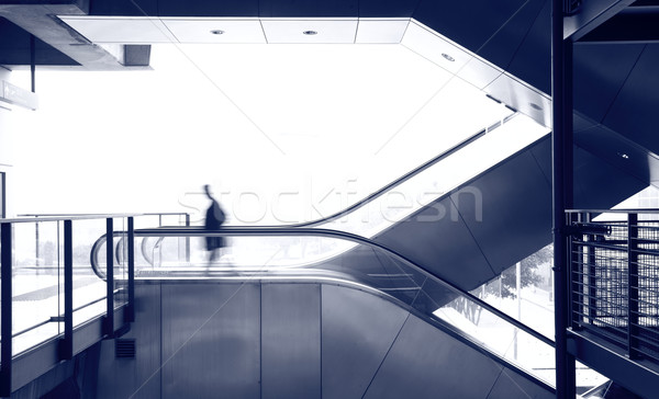 Stock photo: business man move on escalator, blue tone