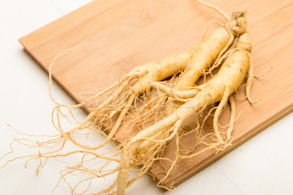 Fresh ginseng stick on the wooden plank Stock photo © leungchopan