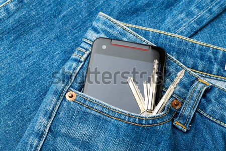 Blue jean pocket with mobile and door key Stock photo © leungchopan