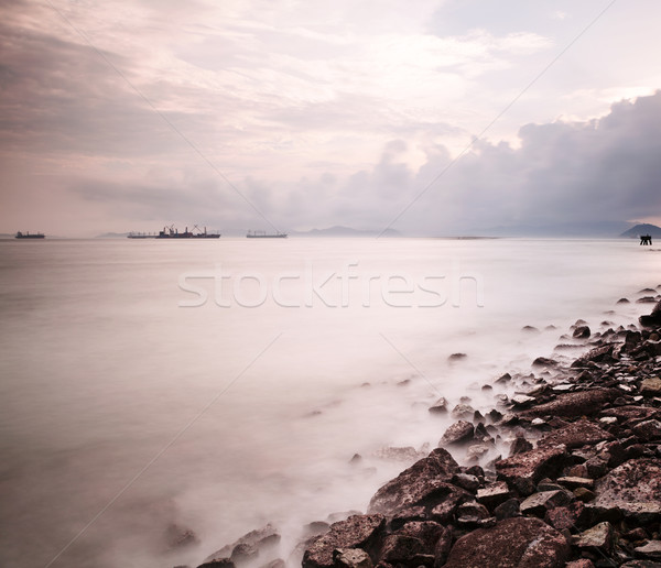 Mar costa ondulação rocha água pôr do sol Foto stock © leungchopan