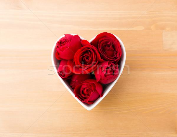 Rose in red inside heart shape bowl Stock photo © leungchopan