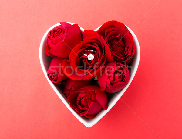 Rose and diamond ring inside heart shape bowl over the red backg Stock photo © leungchopan