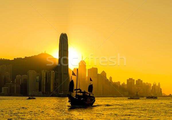 Sziluett Hongkong város naplemente zászló csónak Stock fotó © leungchopan