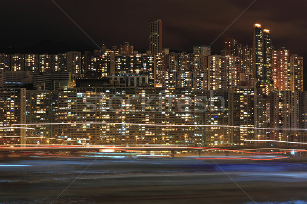 Hong Kong apartment block at night with ship light blur Stock photo © leungchopan