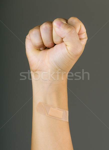 Clenched fist with plaster Stock photo © leungchopan