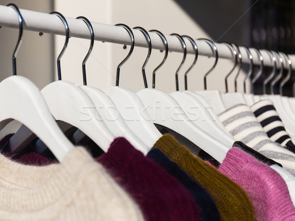 Clothes hang on a shelf in a store Stock photo © leungchopan