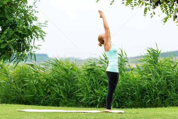 Lady is practicing half moon yoga pose in the nature Stock photo © leventegyori