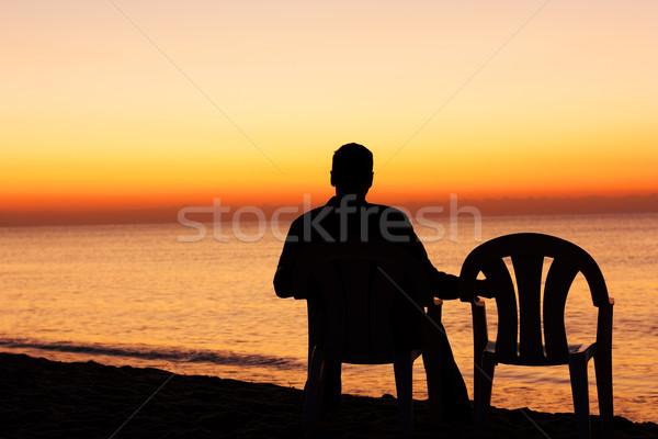 Uomo sedia sola cielo acqua tramonto Foto d'archivio © leventegyori
