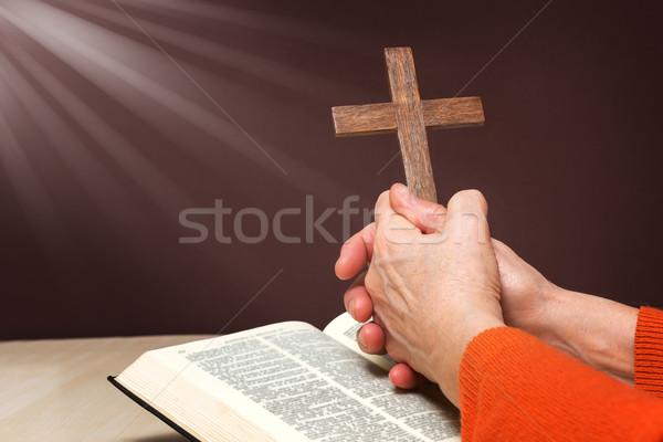 Closeup of wooden Christian cross and hand next on holy Bible Stock photo © leventegyori