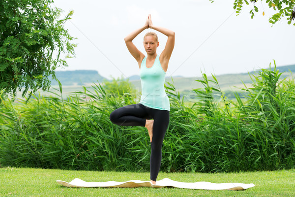 Woman doing tree vrksasana yoga pose, meditating outdoors in nat Stock photo © leventegyori