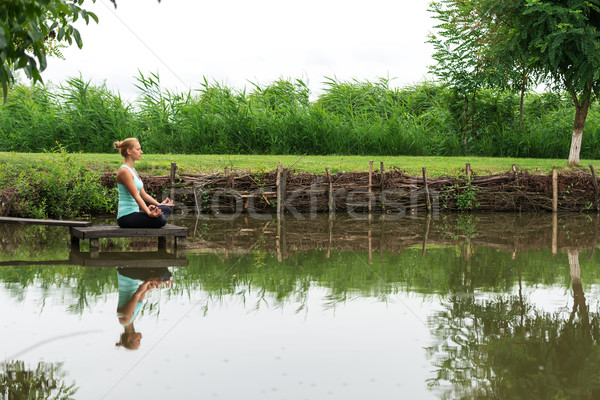 Woman meditating in pose of lotus Yoga Stock photo © leventegyori