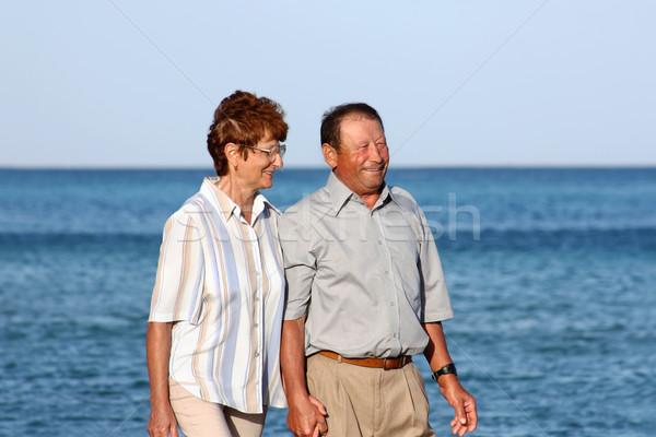 Happy elderly couple walking on the beach Stock photo © leventegyori