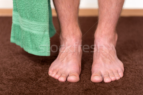 Healthy male feet with towel stepping towards the bathroom. Stock photo © leventegyori