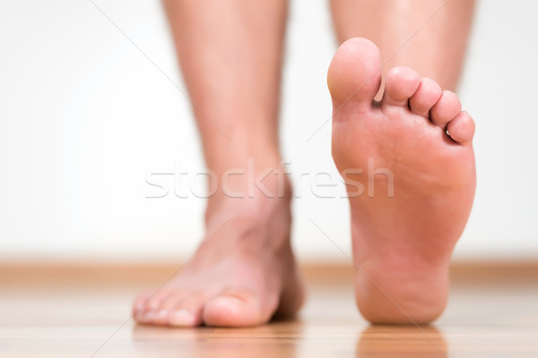 Healthy male feet stepping over home-like background Stock photo © leventegyori