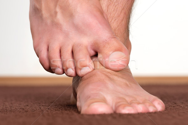 Healthy male feet stepping over home-like background. Stock photo © leventegyori