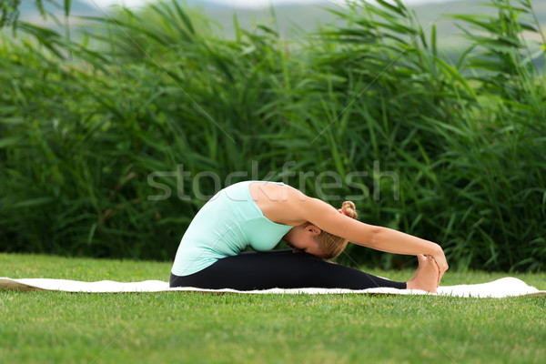 Woman practicing yoga in the park Seated Forward Bend Stock photo © leventegyori