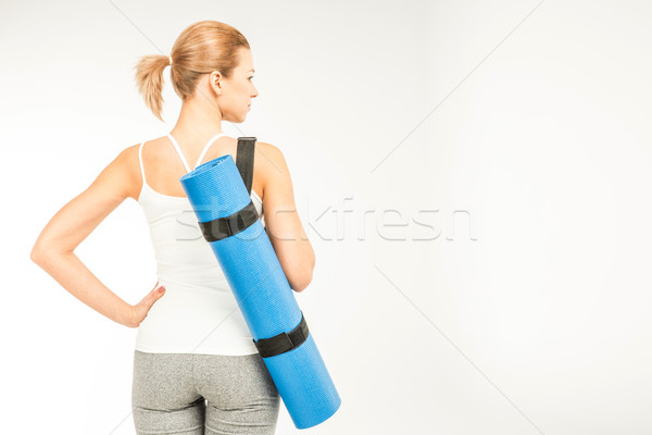 Sportswoman holding yoga mat   Stock photo © LightFieldStudios