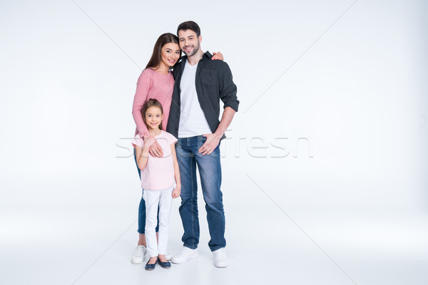 Stock photo: Happy young family with one child standing embracing and smiling at camera