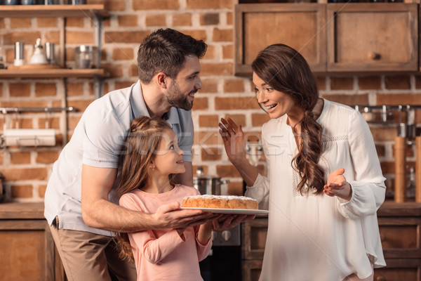 'surprised mother looking at daughter and father with cake on mother's day holiday Stock photo © LightFieldStudios