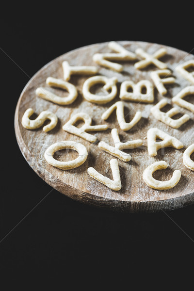 close up view of letters made from cookie dough on wooden board with flour isolated on black Stock photo © LightFieldStudios