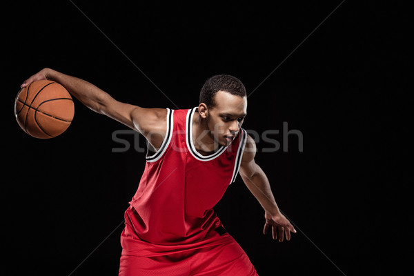 Handsome african american man playing basketball on black  Stock photo © LightFieldStudios
