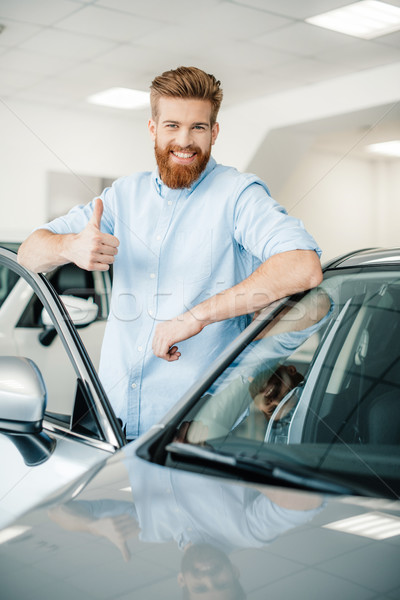 Happy young man leaning at new car and showing thumb up Stock photo © LightFieldStudios