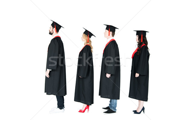 Full length side view of students in academic caps and graduation gowns standing in a row Stock photo © LightFieldStudios